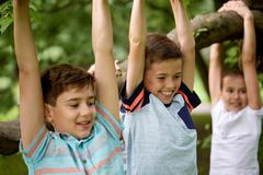 Close up of kids hanging on tree in summer park Stock Photos