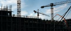 Construction site. A large building, cranes, people working Stock Photos