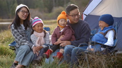 Asian family on a camping trip talking outside their tent Stock Footage