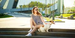 Hipster Fashion Girl with her Dog in the City Stock Photos