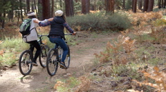 Two women embracing as they ride bikes in forest, back view Stock Footage
