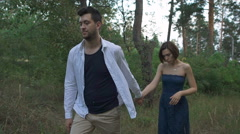 A pleasant man with a beard leads his beautiful wife or girl on a footpath	 Stock Footage