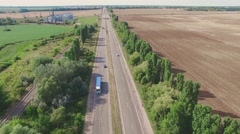 Flight over village fields grain silos, road traffic countryside aerial 4k video Stock Footage