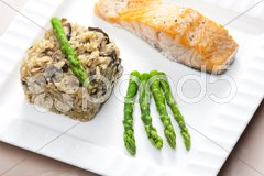 Baked salmon with mushroom risotto and green asparagus Stock Photos