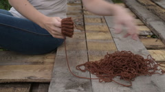 Woman unravelling the knitting outdoors Stock Footage