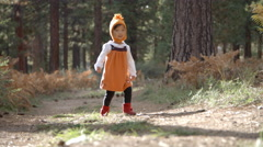 Asian toddler girl walking alone in a forest, front view Stock Footage