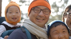 Handheld close up of Asian family of four in a forest Stock Footage