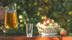 Apple juice and basket with apples on the background of growing apples. Stock Footage