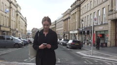 Attractive good looking young blonde business woman using mobile phone in city Stock Footage