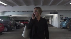 Attractive blonde business woman happy phone call smiling  car park Stock Footage