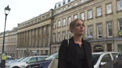 Tired good looking young blonde woman in black coat walking london street Stock Footage