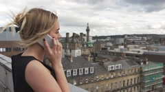 Beautiful blonde woman on rooftop making phone call city mobile london Stock Footage
