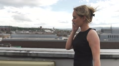 Beautiful blonde woman on rooftop making phone mobile cellphone phone call Stock Footage