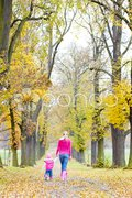 Mother with her daughter in autumnal alley Stock Photos