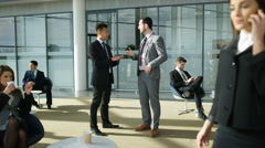 4K Businessmen having a conversation in crowded area of large modern office Stock Footage