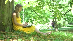 Serious woman working with laptop computer and couple walking in park on Arkistovideo