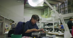 Female worker in electronics factory working on computer testing and repairs Stock Footage