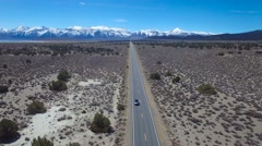 Aerial above a 4WD traveling on a paved road in the Mojave Desert with the Stock Footage