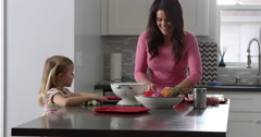Girl and mother talking as they prepare a meal in kitchen, shot on R3D Stock Footage