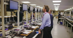 Team of workers in electronics factory working on computer testing and repairs Stock Footage