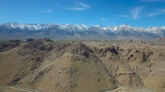A rising aerial over the Alabama Hills of California reveals the towering and Stock Footage
