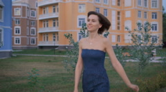 Beautiful young woman in a blue dress, goes on tratuary fun to meet her husband Stock Footage