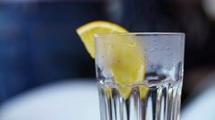 Close up Treatment of Flu. Transparent cup of warm water with lemon Stock Footage