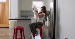 Female couple sitting in kitchen holding their baby girl, shot on R3D Stock Footage