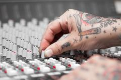 Closeup of hands covered with tattoos working on mixer console, twisting knobs Stock Photos