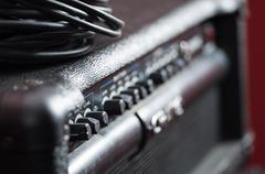 Closeup amplifier with row of buttons and knobs, descriptions turning blurry Stock Photos