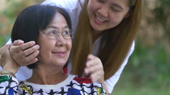 Asian woman closes senior's eyes with hands for surprise, Slow motion shot Stock Footage