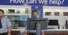 Sales people working on computers in consumer electronics store showroom Stock Footage
