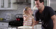 Girl putting cake mix mix on dad's nose while they bake together, shot on R3D Stock Footage
