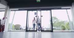Couple entering large consumer electronics store showroom Stock Footage