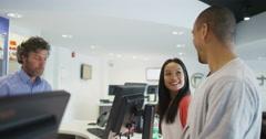Helpful salesman serving customers in consumer electronics store showroom Stock Footage