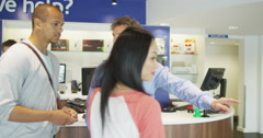 Helpful salesman serving customers in consumer electronics store showroom Stock Footage