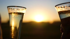 Wine glasses clink at sunset Stock Footage
