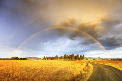 Rainbow in Tuscany, cypress trees and rural road. Maremma, Italy. Stock Photos