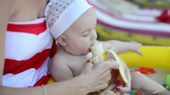 Baby girl is eating a banana. Stock Footage