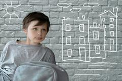 Child's drawing. Teenage boy with a road backpack sitting on brick wall Stock Photos
