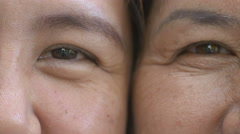 4K : Close up on eyes of Asian mother and daughter faces Stock Footage