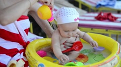 Child play and having fun in inflatable rubber pool on a sunny day Stock Footage