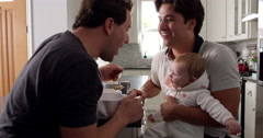 Male couple having breakfast with baby girl in their kitchen, shot on R3D Stock Footage