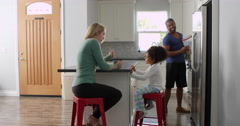 Mixed race couple and daughter talk in kitchen, full length, shot on R3D Stock Footage