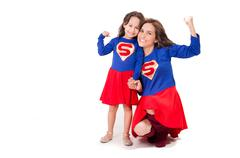 Mother and young daughter happily interacting together, both dressed in superman Kuvituskuvat