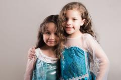 Adorable big and little sister wearing matcing blue dresses posing together Stock Photos