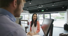 Helpful staff serving customers in consumer electronics store showroom Stock Footage