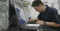 Staff member working on laptop computer in consumer electronics store showroom Stock Footage
