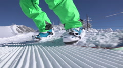 SLOW MOTION CLOSE UP: Extreme snowboarder carving on groomed snow in ski resort Stock Footage