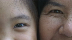 4K : Close up on eyes of Asian girl and senior woman faces Stock Footage